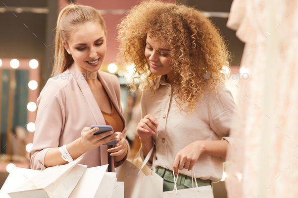 Young Women Using Smartphone in Boutique - Stock Photo - Images