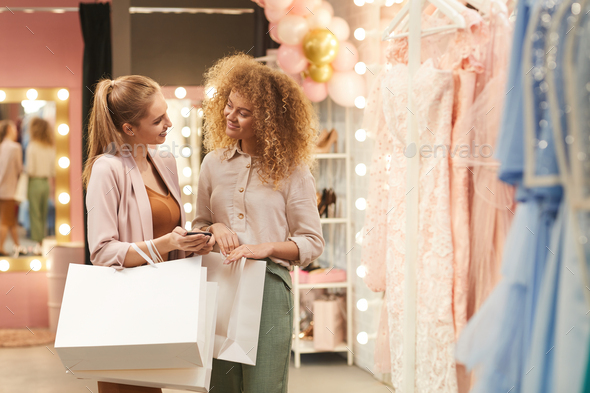 Two Women Holding Shopping Bags in Boutique - Stock Photo - Images