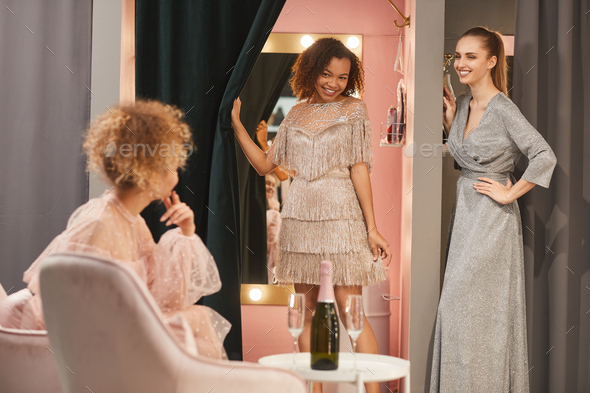 Young Women Trying on Gowns in Dressing Room - Stock Photo - Images