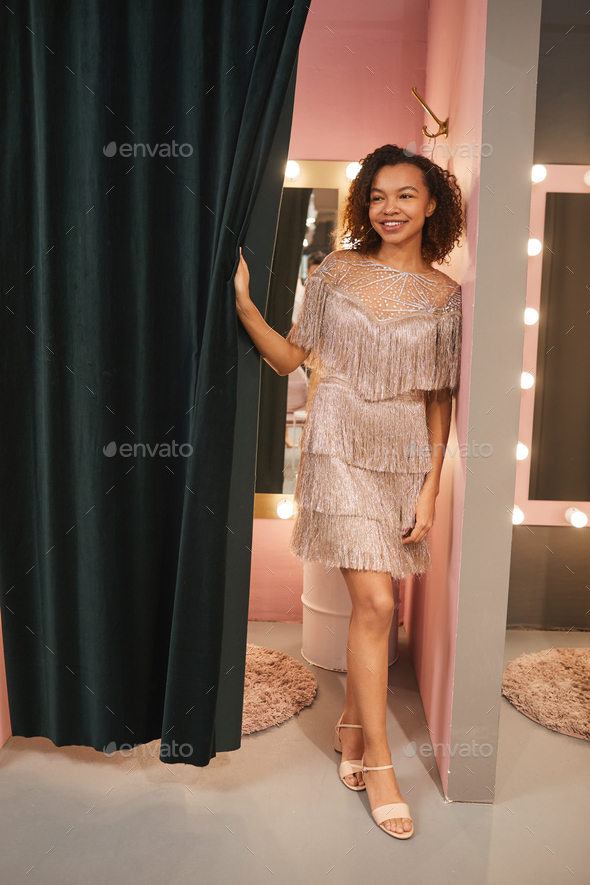 Mixed-Race Woman Trying on Gowns in Dressing Room - Stock Photo - Images