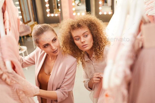 Two Young Women Choosing Dresses in Clothing Boutique - Stock Photo - Images