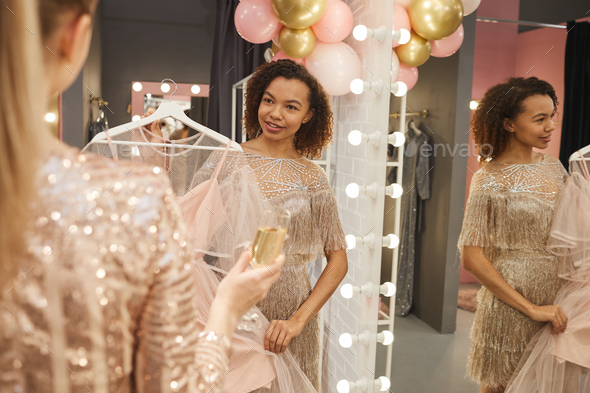 Two Young Women Trying on Dress in Boutique - Stock Photo - Images