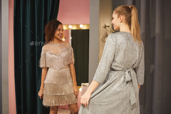 Girlfriends Trying on Gowns in Dressing Room - Stock Photo - Images