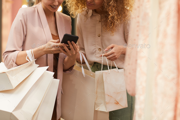 Two Young Women Using Smartphone in Boutique - Stock Photo - Images