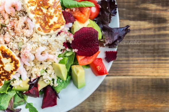 Warm Salad from Brown Rice, Quinoa, Prawns, Halloumi and Veg - Stock Photo - Images