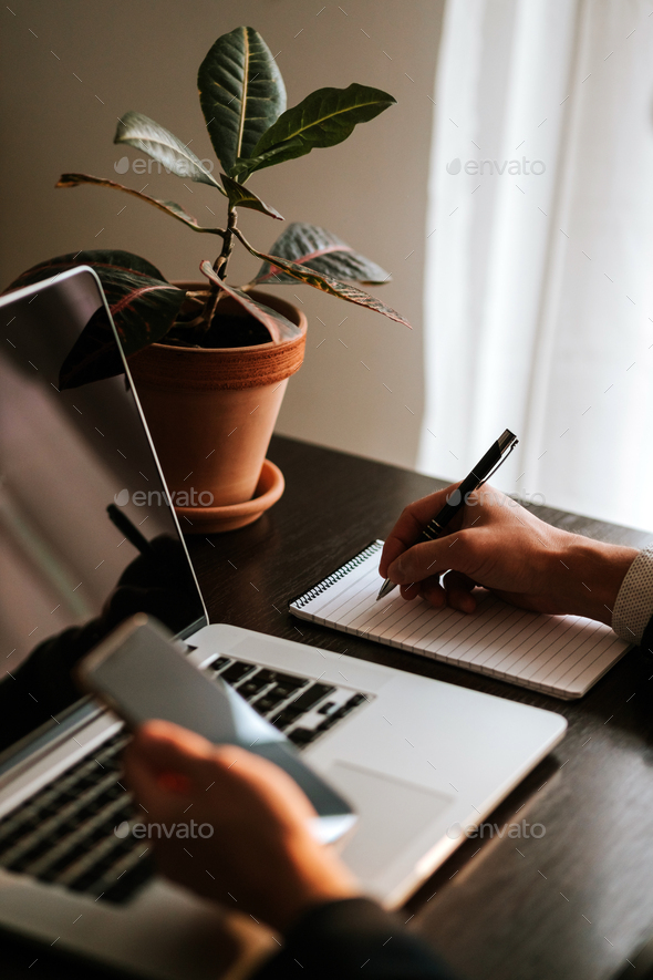 Businessman making notes and using gadgets - Stock Photo - Images