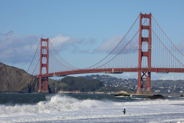 A lone fisherman fishes in the waves next to the famous Golden Gate Bridge in San Francisco. - Stock Photo - Images