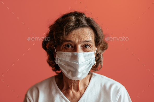 Senior woman against pink background looking straight at camera wearing face mask. - Stock Photo - Images