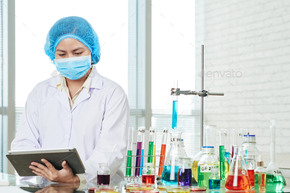 Laboratory worker filling form on tablet computer - Stock Photo - Images
