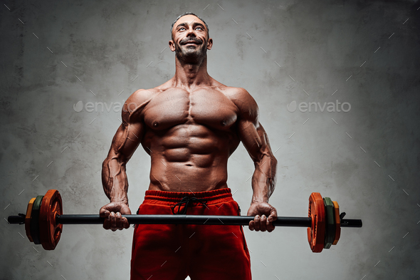 Healthy and energetic man doing biceps exercises, focused and looking strong with barbell - Stock Photo - Images