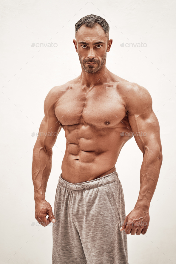 Shirtless sporty caucasian male isolated on a white concrete background - Stock Photo - Images