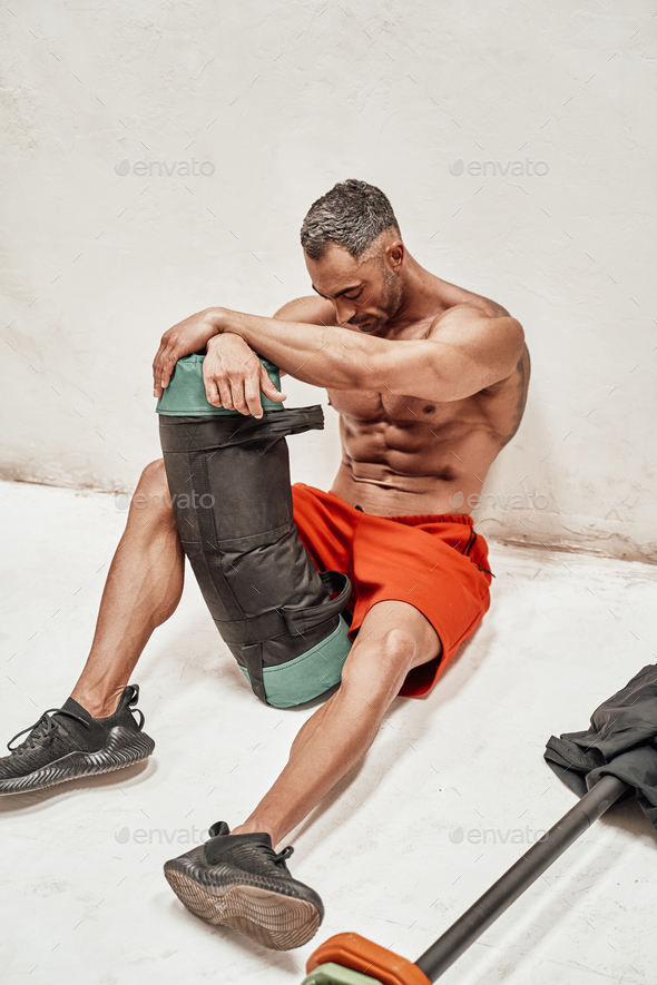 Handsome adult sportsman wearing sportswear posing for a camera while holding a weight bag - Stock Photo - Images
