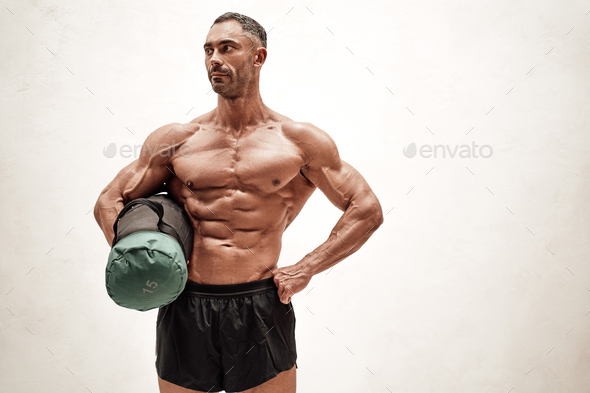 Strong adult sportsman with naked torso wearing shorts, holding a weight bag in a bright studio - Stock Photo - Images