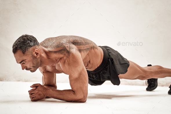 Buffed sportsman posing in a bright studio, while doing an exercise on the floor - Stock Photo - Images
