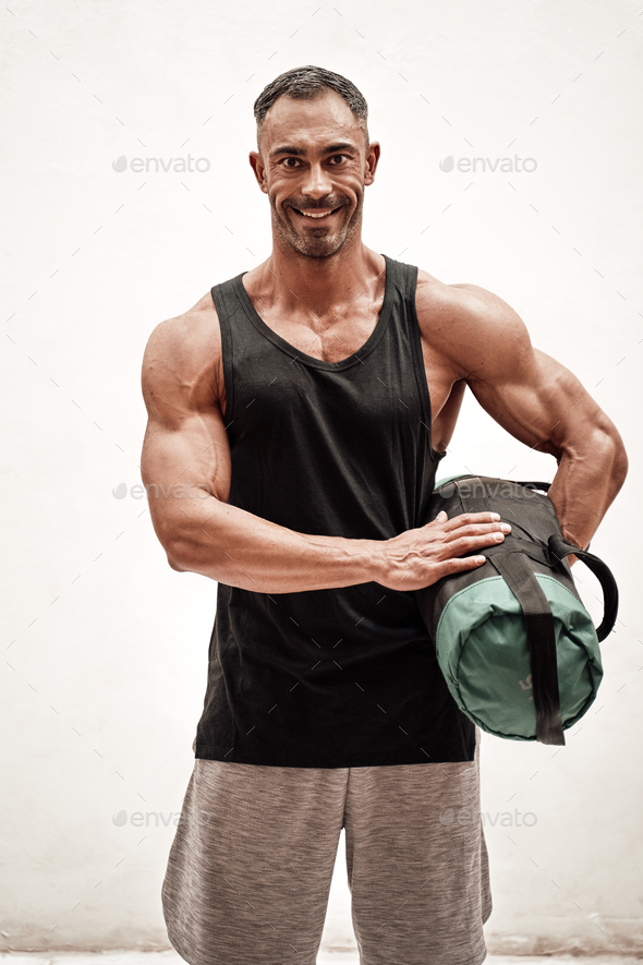 Strong and muscular athlete posing in a bright studio with a weight bag looking fresh - Stock Photo - Images