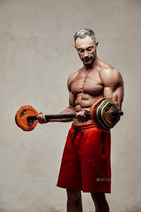Handsome adult sportsman wearing sportswear posing for a camera while holding a barbell - Stock Photo - Images