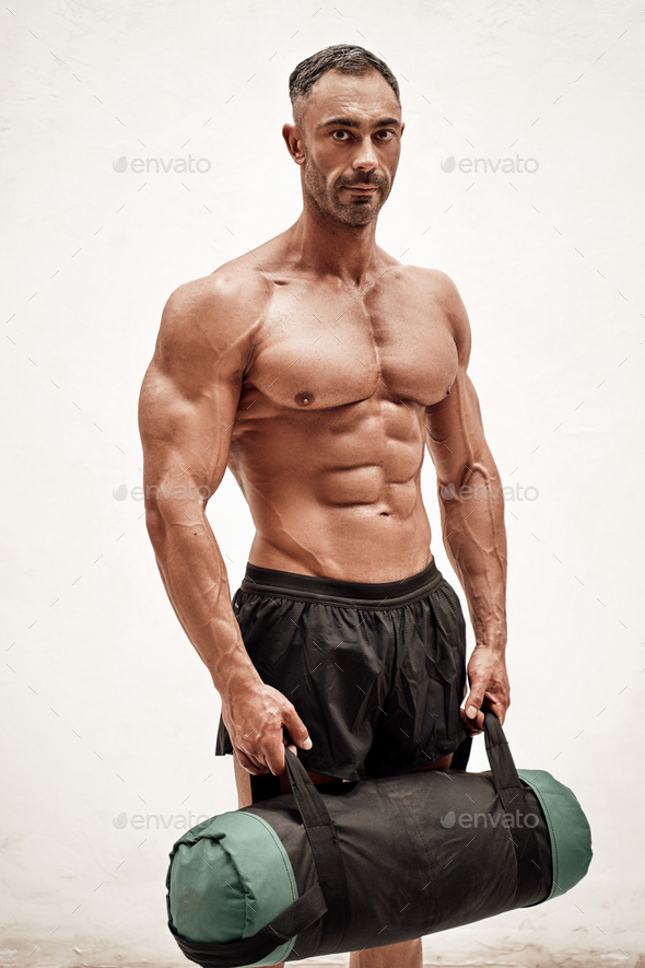 Handsome athlete wearing sportswear posing with sand bag and looking at the camera in a dark studio - Stock Photo - Images