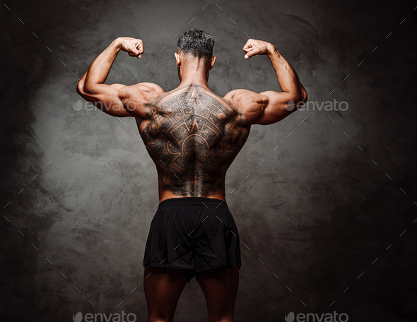 Close-up photo of a shirtless inked sportsman, standing backwards, in a dark studio - Stock Photo - Images