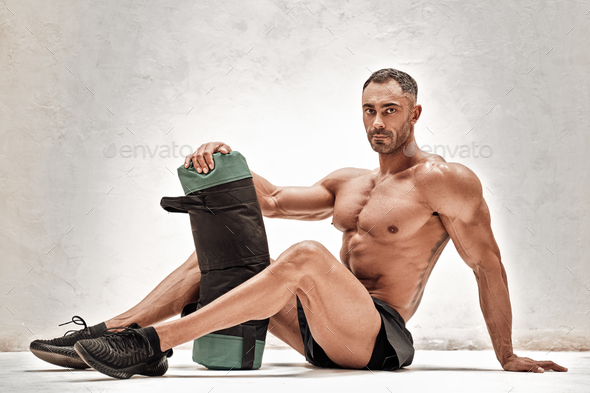 Embossed and exhausted fitness couch posing in a studio with sportsgear - Stock Photo - Images
