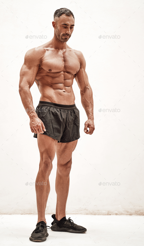 Shirtless sporty caucasian male isolated on a white concrete background looking down - Stock Photo - Images