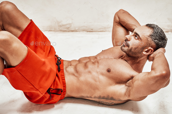 Buffed sportsman posing in a bright studio while doing a press pump exercise - Stock Photo - Images