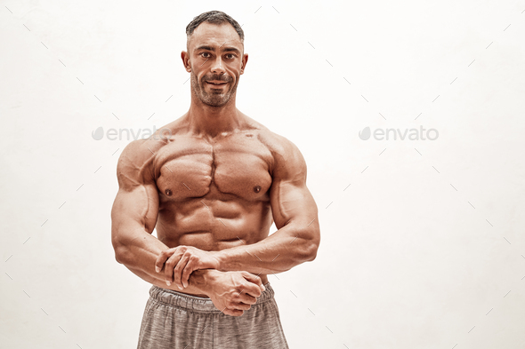 Close-up photo of a sportsman, showing his chest muscles in a bright studio - Stock Photo - Images