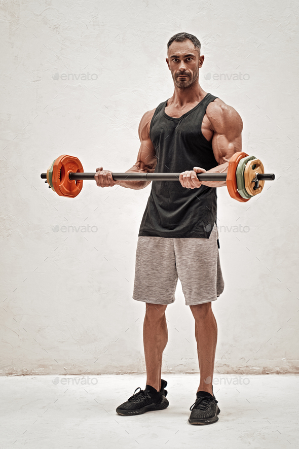 Full height portrait of a sportsman, flexing with a barbell in a bright studio - Stock Photo - Images