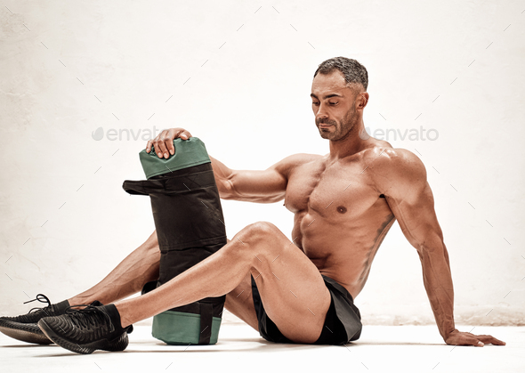 Strong adult man relaxing on the floor with a weight bag after workout - Stock Photo - Images