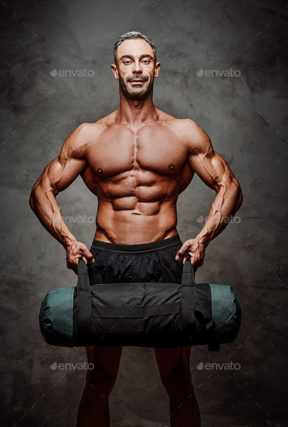 Athletic man isolated on a white background doing and exercise with a weight bag - Stock Photo - Images
