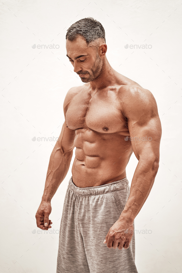 Strong and powerful man bodybuilder looking down in a bright studio - Stock Photo - Images