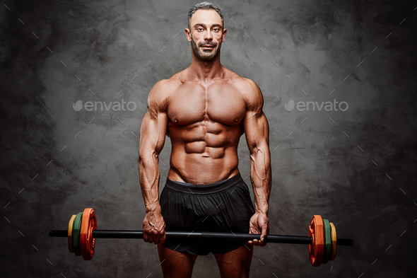 Embossed fitness couch posing in a studio with fitness gear - Stock Photo - Images