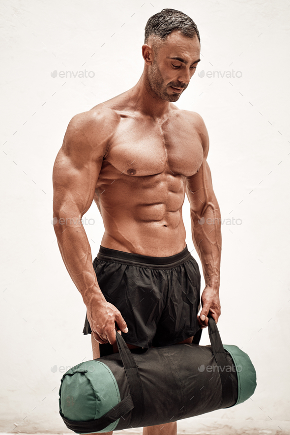 Sportive adult male wearing sportswear posing with a weight bag and looking down in a bright studio - Stock Photo - Images