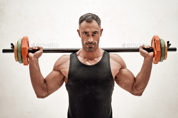 Close-up photo of a sportsman, flexing with a barbell in a bright studio - Stock Photo - Images