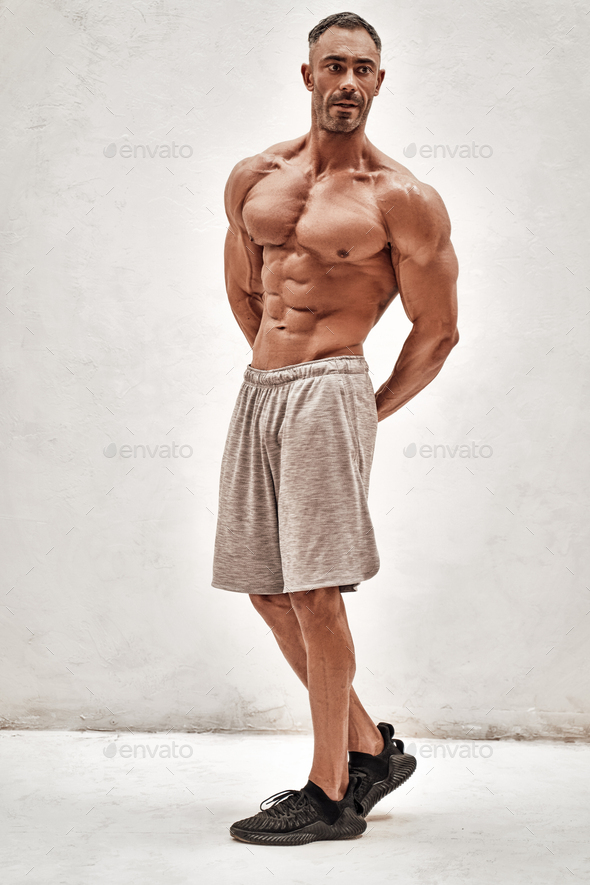Embossed fitness couch showing his muscles looking powerful - Stock Photo - Images
