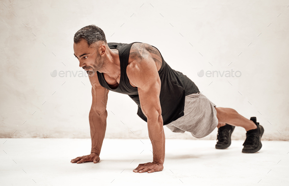 Strong and muscular athlete posing in a bright studio while doing a plank excersise - Stock Photo - Images