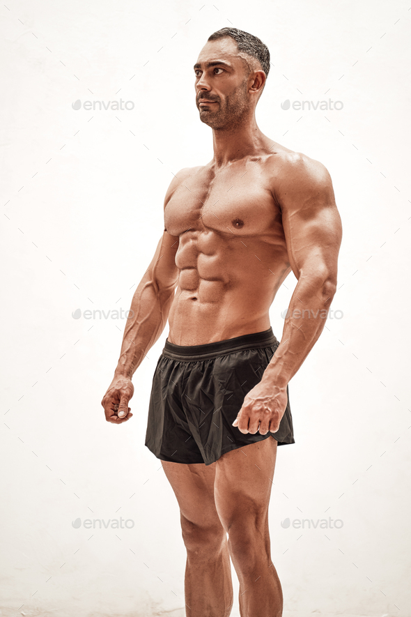 Shirtless sporty caucasian male isolated on a white concrete background showing athletic body - Stock Photo - Images