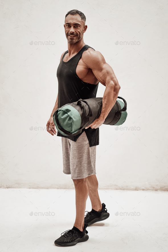Buffed sportsman posing in a bright studio with a weight bag - Stock Photo - Images