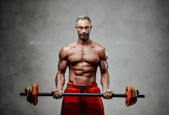 Shirtless adult male bodybuilder doing a biceps exercise with a barbell in a bright studio - Stock Photo - Images