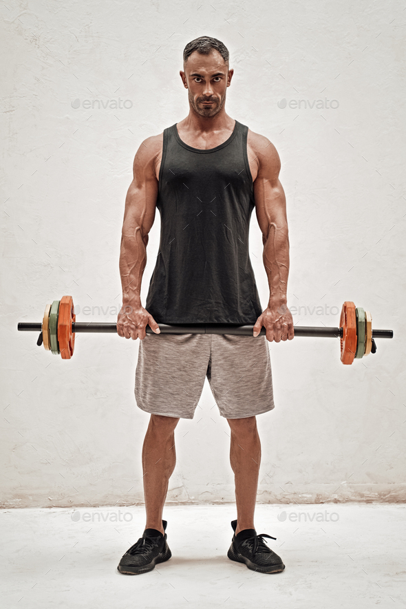 Strong and sportive fitness trainer holding a barbell isolated in a studio - Stock Photo - Images