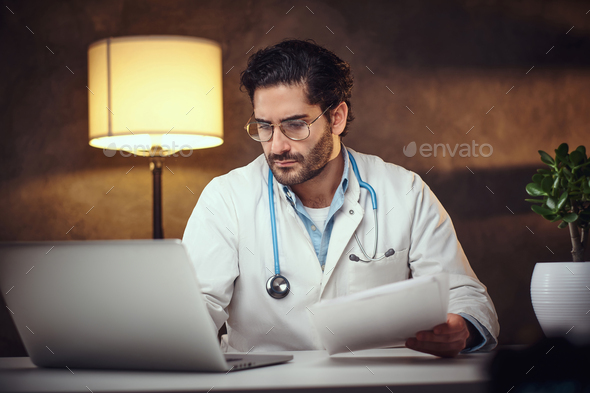 Busy doctor in his office is working with paperworks - Stock Photo - Images