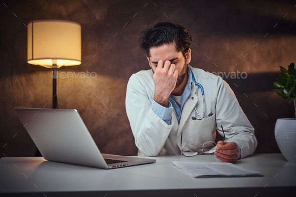 Tired medic is sitting next to the table - Stock Photo - Images