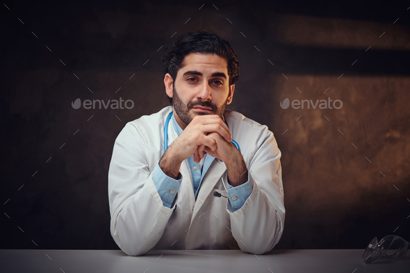 Tired student intern is sitting next to the table - Stock Photo - Images