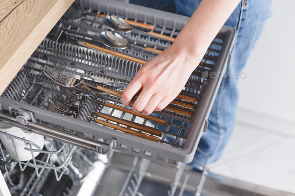 Woman puts cutlery in the dishwasher. - Stock Photo - Images