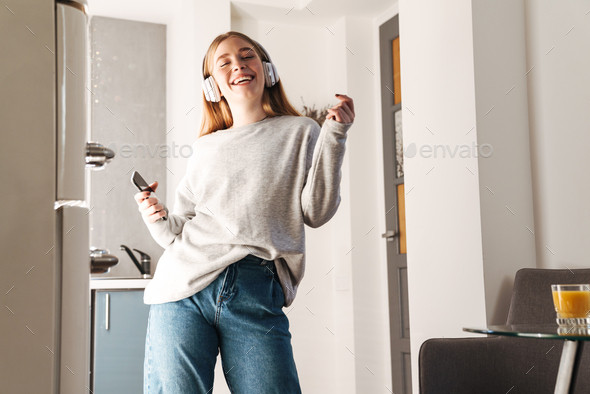 Girl holding mobile phone listening music with headphones - Stock Photo - Images