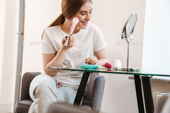 Concentrated girl indoors at home with mirror apply makeup - Stock Photo - Images