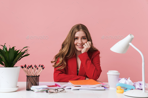 Woman sit at the table over pink wall background. - Stock Photo - Images