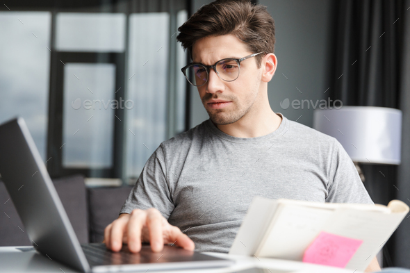 Man indoors using laptop computer holding documents. - Stock Photo - Images