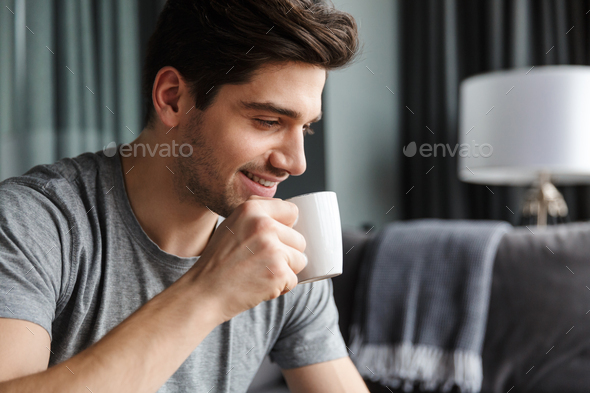 Close up of a smiling young bearded man drinking tea - Stock Photo - Images