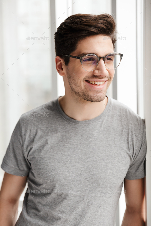 Optimistic young man indoors at home looking at window. - Stock Photo - Images