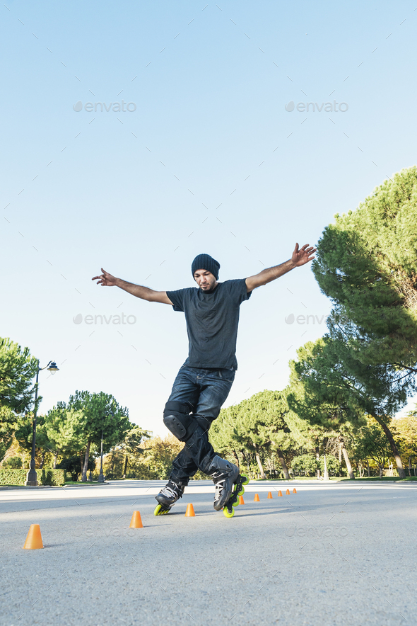 Urban young man on roller skates on the road at summer time - Stock Photo - Images